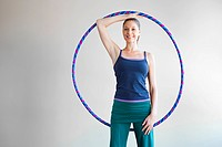 Woman holding plastic hoop doing pilates