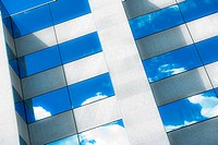 clouds relection in a glass facade of a high rise building