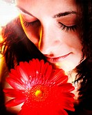 Macro image of a girl face with a red flower