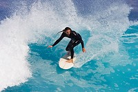 Surfer well balanced rides stunning blue wave