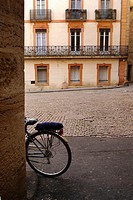 A bicycle left leaning against a wall in Pezenas, France.