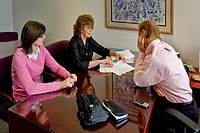 Two female office workers discuss a client´s tax return with their financial consultant boss in Irvine, California.
