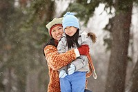Chinese mother hugging daughter in the snow