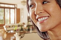 Smiling Asian woman in living room