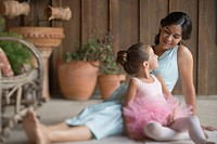 Mother sitting on porch with ballerina daughter