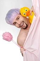 Man in the shower with large rubber duckie and back scrubber