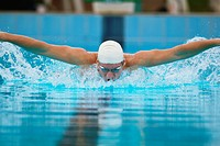 Young adult man swimming butterfly stroke