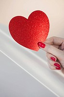 Close up of woman´s fingers with red nail polish holding red heart