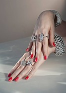 Close up of woman´s hands with red nail polish and diamond jewelry
