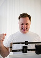 USA, Jersey City, New Jersey, man on weight scales laughing