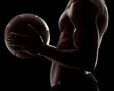 Studio shot of shirtless man holding basketball, mid section