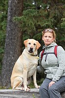 Portrait of woman hiker and her Yellow Labrador Retriever dog, sitting on a fallen log. Banff National Park, Alberta, Canada.