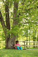 Younge girl reading a book under a tree in Northern Alberta, Canada.