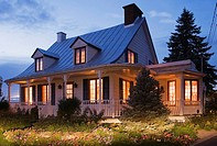 Old Canadiana circa 1821 cottage style wooden siding Residential Home at dusk, Quebec, Canada