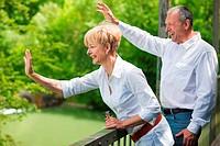 Älteres Paar auf Brücke winkt