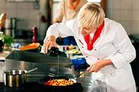Köchin in Restaurantkücke schmeckt ab
