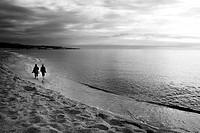 Couple walking on beach, Mataro, Catalonia, Spain