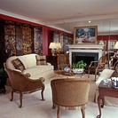 FIREPLACE _ formal living room. Mirrored wall, molding, crown molding, red walls, Asian folding screen, animal print chairs, ivory loveseat, fireplace...