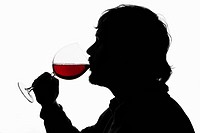 A silhouetted man drinking red wine from a wineglass