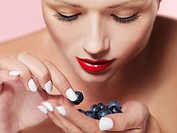 A woman choosing a blueberry from her palm