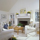 LIVING ROOMS _ White on white, slip covers on overstuffed furnishings, fireplace, sliding glass doors on either side. Oak coffee table, curtains on Fr...