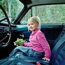 Girl holding flowers sitting in car, smiling