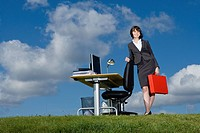 Businesswoman with red briefcase at desk in grass field