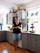 Mature woman standing in kitchen, peeling apple
