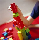 Child building a tower using toy bricks, Sweden.