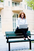 Woman sitting on a bench using her laptop, Stockholm, Sweden.
