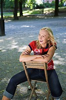A smiling woman sitting on a chair outdoors, Stockholm, Sweden.