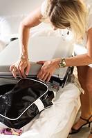 A scandinavian woman packing a suitcase.