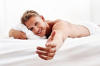 Man lying in bed and extending his hand