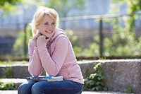 Portrait of smiling teenage girl sitting on stone steps