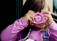 A little girls tries to be a photographer with a toy camera
