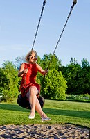 Mature woman on swing made of car tire
