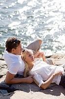 Couple lying on rock beside sea