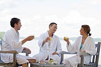 People in bathrobe enjoying breakfast beside lake
