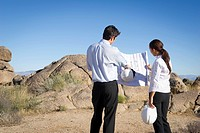 Business people looking at blueprints in desert