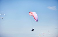 Person paragliding against blue sky