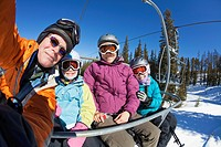 Family riding ski lift together