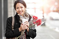 Mixed race woman holding coffee and bouquet of flowers