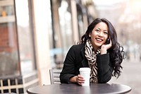 Mixed race woman talking on cell phone and drinking coffee
