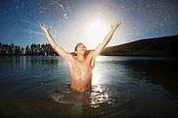 Excited man splashing water in lake