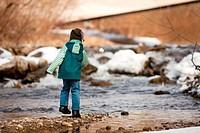 Kind mit Schneeball am Fluss