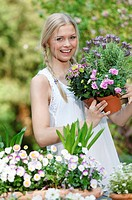 woman working in garden holding flowers in hands