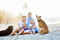 portrait of family on beach with dogs