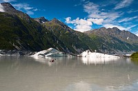 Man kayaking amongst icebergs in the lake at Valdez Glacier's terminus, Southcentral Alaska, Summer