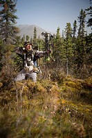 Male bow hunter aims with a compound bow while bow hunting in a Black Spruce forest in the Eklutna Lake area, Chugach Mountains, Chugach State Park, S...
