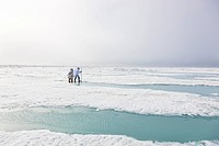 Two Inupiaq Eskimo hunters wearing their Eskimo parka´s Atigi carry a rifle and walking stick while walking over the shore ice along the Chukchi Sea, ...